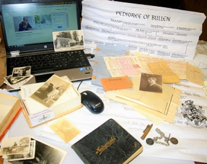 A laptop with a genealogy website on the screen, surrounded by papers and photograph albums