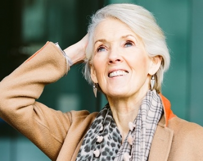 Joanna Trollope in a beige coat looks up to the sky