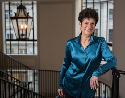 Margaret Fingerhut, a brunette woman wearing a blue silk shirt leans on a stairway banister