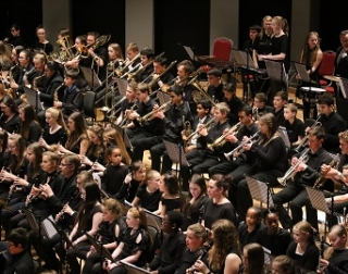Students are sat in an orchestra, holding brass instruments.