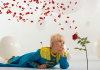 The Little Prince, dressed in a blue uniform, lays on a white floor and gazes at a rose which is drifting petals into the breeze