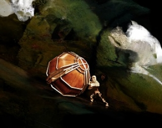 A mechanical puppet pushes a wooden boulder in front of a brooding, swirling sky