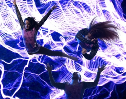 Two female dancers spin in the air against a background of purple electricity