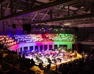 A full concert hall, lit with multiple colours of lighting