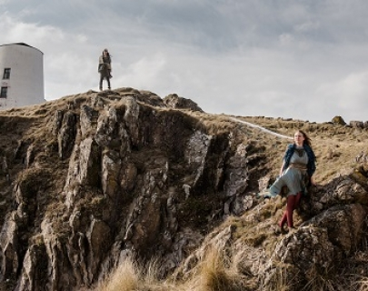 Two women stand on a rocky outcrop, a lighthouse behind them