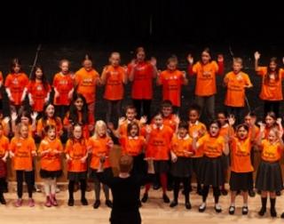 A chorus of children in orange t-shirts throw their arms in the air