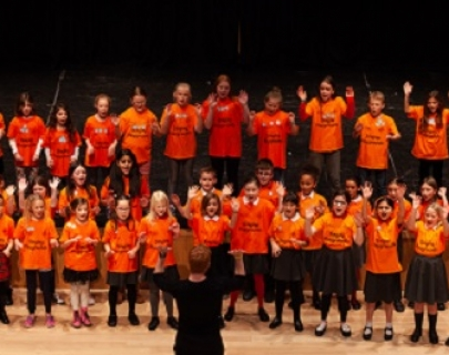 A chorus of children in orange t-shirts throw their arms in the air