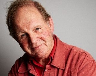 Author Michael Morpurgo sits against a grey background, wearing an orange shirt and looking at the camera.