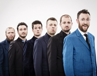 Six men wearing suits stand in a row, pulling faces at the camera.