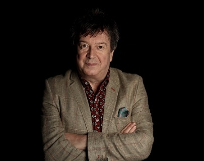 Stuart Maconie stands against a black background with his arms crossed wearing a checked suit