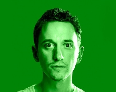A head shot of John Robins with a green filter laid over the top, so he and the background both appear green.