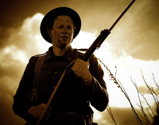 A soldier with a rifle, photographed in sepia tones