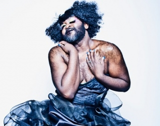 La Gateau Chocolat, a bearded black man with glitter in his hair, in a low cut black dress