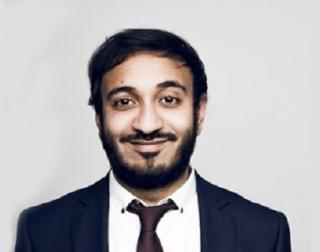 Comedian Bilal Zafar wears a suit against a grey background