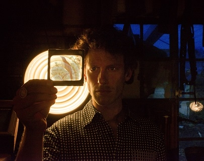 A man in a checked shirt holds up a coloured slide of a nightingale, with a bright light in the background