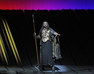 A man with long hair and an eye patch wears armour, standing on stage