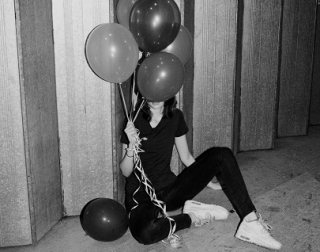 Black and white. A young woman sits on the floor, wearing black clothes and white shoes, with her face covered by a bunch of balloons.