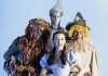 Dorothy, Tinman, The Scarecrow and the Lion all in costume and looking straight at the camera lens on a sky blue background.