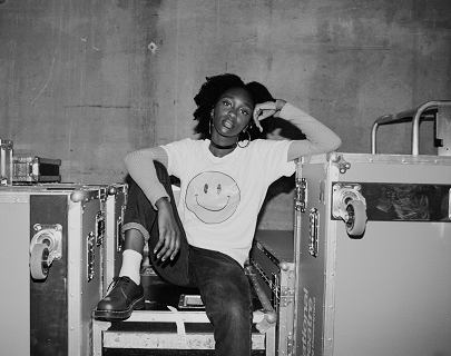 Black and white. A young woman sits on top of some crates, wearing a white t shirt with a smiley face on it.