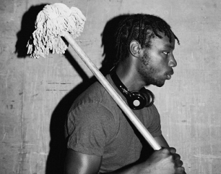 Black and white. A young man holds a mop over his shoulder and looks off to the right.