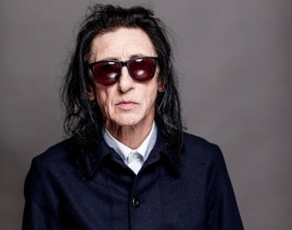 Dr John Cooper Clarke - a man with long hair and dark glasses - wears a dark blue and white shirt against a grey background. He is looking at the camera.