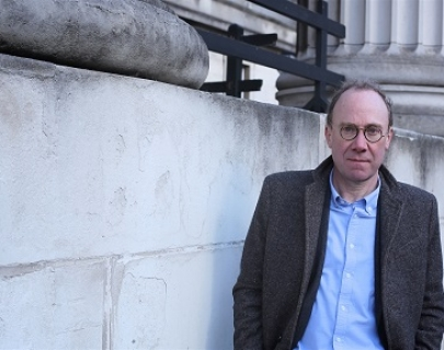 Ben Macintyre photographed with round glasses and wearing a blazer