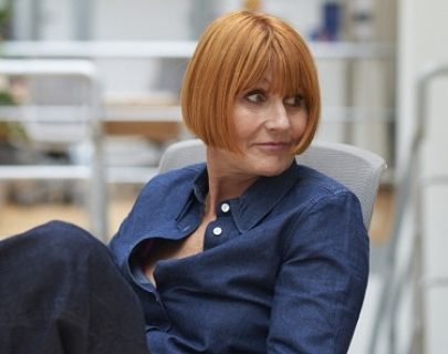 Mary Portas, sitting in a sunny room, wearing a blue shirt