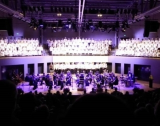 An orchestra on stage, with a choir dressed in white above them.