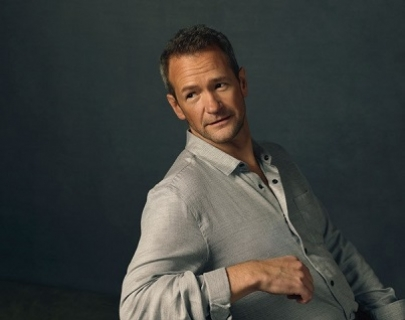 Alexander Armstrong wears a grey shirt and leans back, looking to the left of the camera