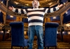 Richard Herring in a horizontally striped jumper, with his arms spread, in a theatre auditorium