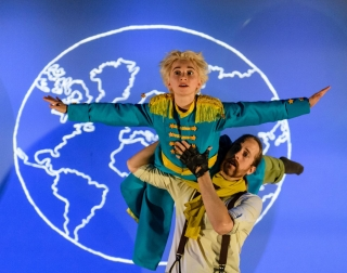The Little Prince, dressed in a blue uniform, is lifted against a backdrop of the earth.