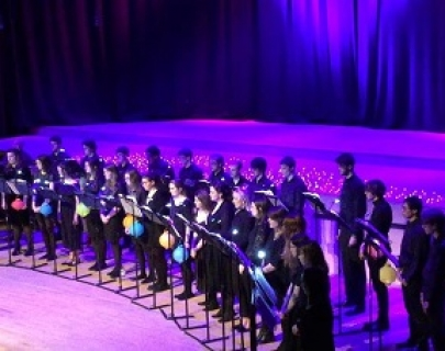 A student chamber choir, lit in purple lighting