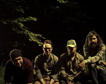 The four members of Turin Brakes in outdoors clothing sitting in the forest