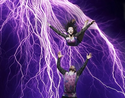 A female dancer thrown in the air by her male co-dancer with a purple electric light in the background