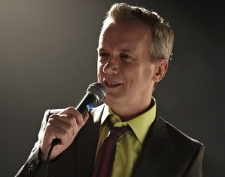 Frank Skinner holding a microphone performing his stand-up