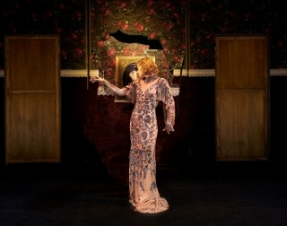 A blonde woman with short curly hair is acting in a long and floaty pink dress with sequins all over it