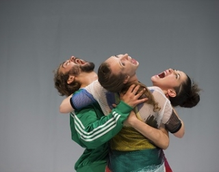 Three dancers - 2 women and 1 man - embracing and screaming in a circle