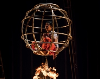 A child in a circular cage hanging above a fire installation and a woman dancing around it expressively, on a bed of exotic flowers