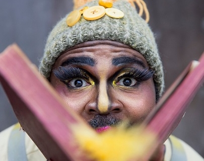 A man with a bobble hat, fake eyelashes and golden eye-shadow blowing yellow feathers from a book looking at the viewer directly