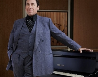 Jools Holland in a blue suit standing in front of a black piano