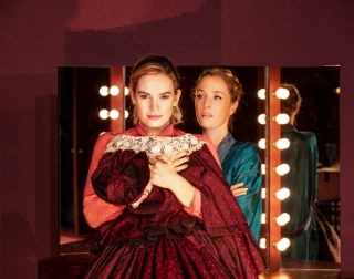 Two women (Lily James and Gillian Anderson) standing in front of a stage mirror