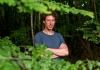 Sam Lee looking at the camera with his arms crossed in a foliage of woods