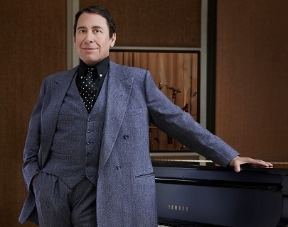 Jools Holland wears a blue suit and stands in front of a piano.