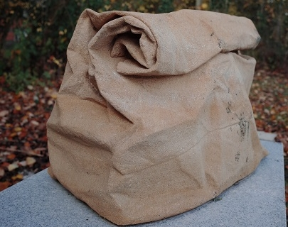 A brown stone sculpture of a takeaway bag.