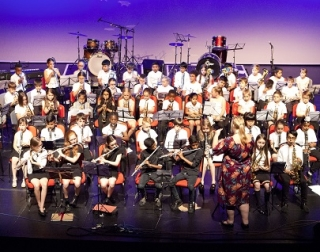 A group of school children perform in an orchestra onstage