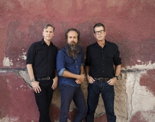 Three men in shirts and jeans lean against a red wall and stare at the camera