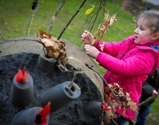 A young girl decorates one of the the campus sculptures with leaves and twigs