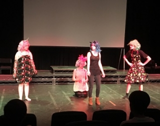 4 young performers on stage in colourful costumes