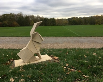 A stone origami hare on a green field