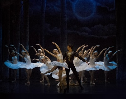 A male and female ballet dancer perform in Swan Lake, with ballet dancers in white behind them